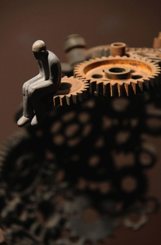 Man Sitting on Gears Symbolizes the Relationship Between Humans and Machines