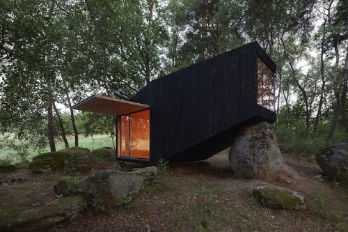 Small Retreat House in the Forest Designed to Rest on a Giant Boulder