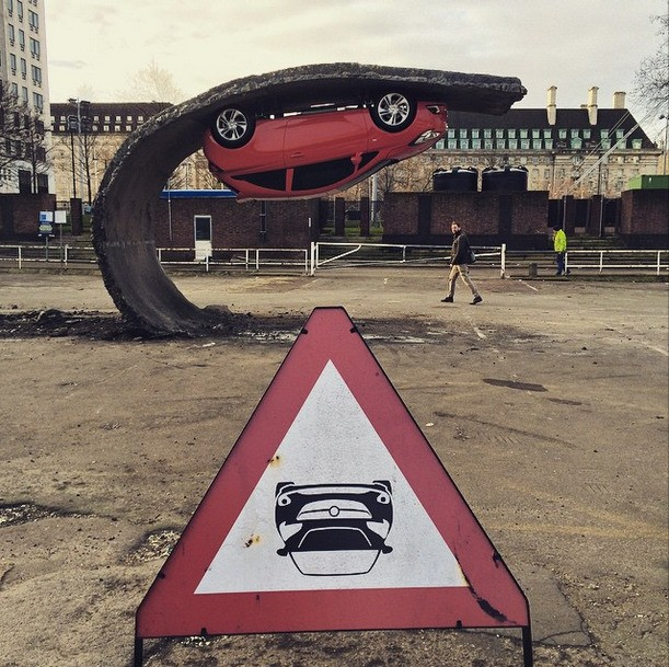 Artist Creates the Illusion of an Upside Down Car Stuck to a Wave of Road