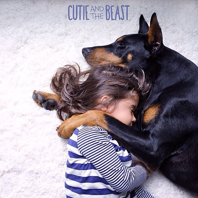 Adorable Photos Showcase Loving Bond Between 3-Year-Old and Her Doberman