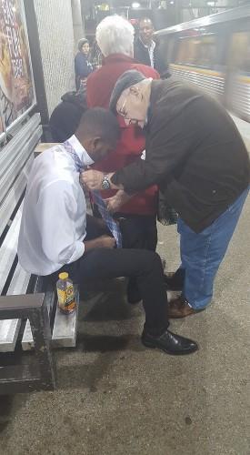Kind Elderly Stranger Teaches Young Man How to Tie Necktie in Train Station