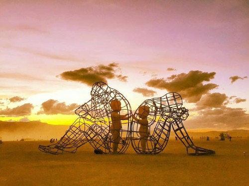 Burning Man Sculpture Reveals Inner Child Glowing within Giant Wire-Framed Adult Bodies