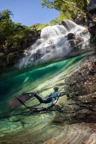 Freediving under the paradise water fall Photo by Marc Henauer — National Geographic Your Shot