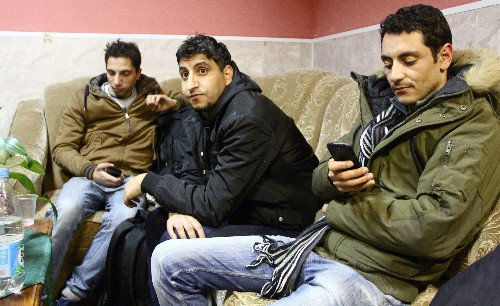 Nabil (r), a migrant from Tunisia, waits with friends in the Russian Nordic town of Nickel, for a chance to get across to Norway.