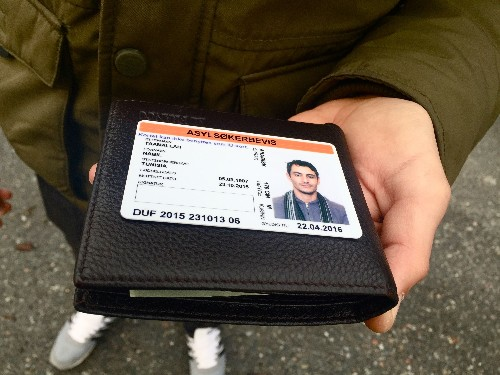 Nabil, a migrant from Tunisia, displays his temporary visa to Norway.