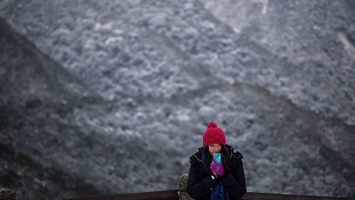 A woman takes photographs as snow is seen at the background on the Yangmungshan National Park during a snowfall in Taipei, Taiwan. Taiwan experienced a sudden drop in temperature over the weekend.