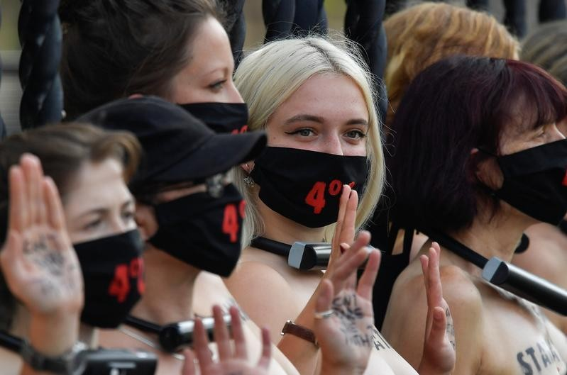 Bare-chested women lock themselves to UK parliament in climate protest