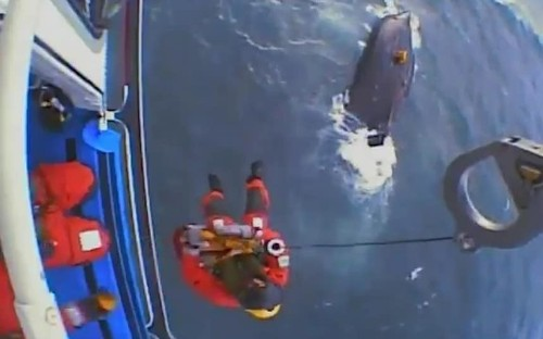 Incredible moment Coastguard rescues fishermen stranded on hull of capsized boat