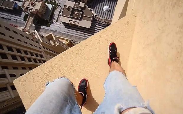 Parkour runner jumps between skyscraper ledges at dizzying height