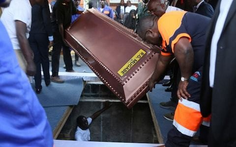 Robert Mugabe buried in a steel coffin encased in concrete as family claims people are 'after his body'