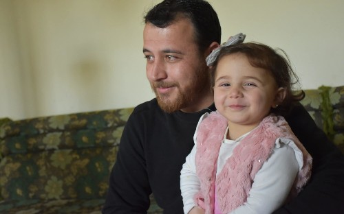 Father teaches young daughter to laugh at bombs to help cope with Syrian war