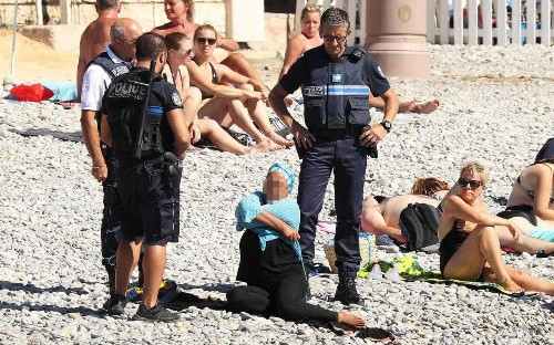 Woman forced to remove burkini on Nice beach by armed officers