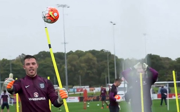 England goalkeeping coach Dave Watson impales football on spike during training with Joe Hart