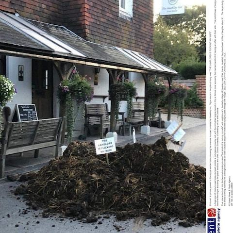 Huge pile of manure with signs saying 'the landlord is f---ing my wife' appears outside country pub