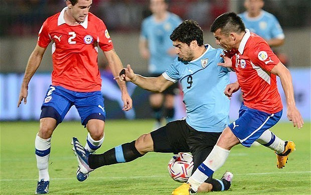 Luis Suarez courts controversy with punch in World Cup clash against Chile