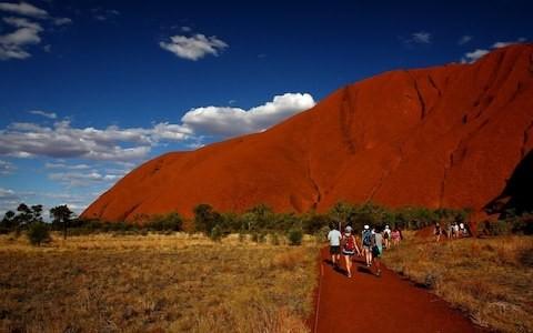 Thousands climb Uluru before sacred Australian site closes to tourists