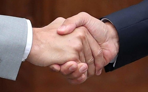 Handshakes may spread coronavirus through touch and 'tidal breath' warn experts