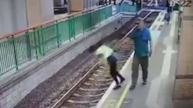 Shocking moment man pushes woman onto train tracks in Hong Kong