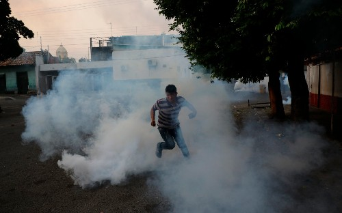 Soldiers unleash tear gas during trouble at Venezuela border, in pictures
