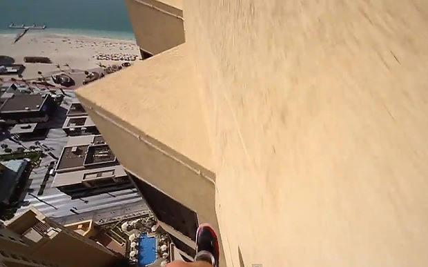 Parkour runner jumps between skyscraper ledges at dizzying height