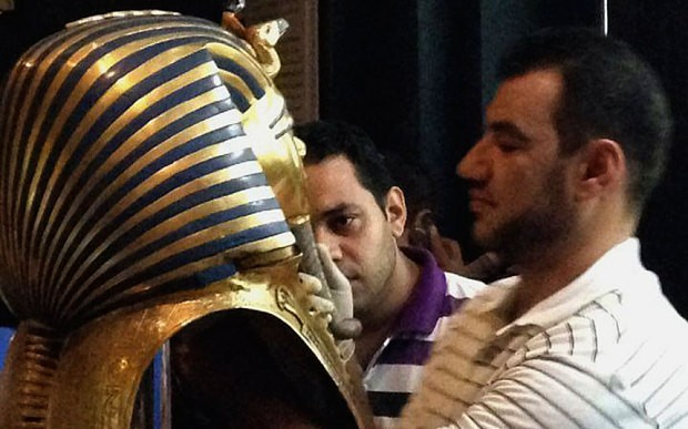 Tutankhamun's mask being fixed after botched glue repair