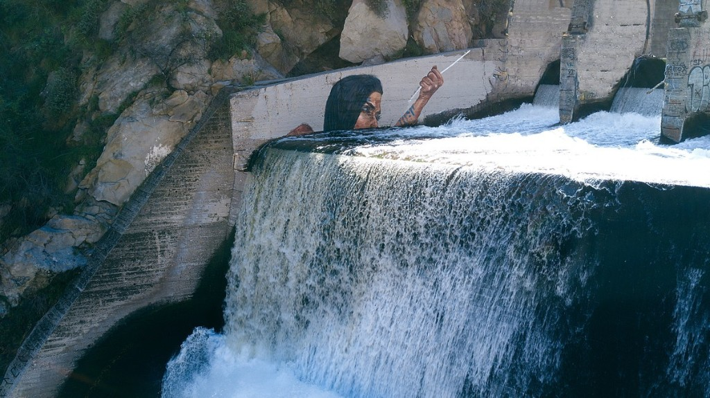 Watch a Paddle Boarding Artist Paint a Mural on a Waterfall
