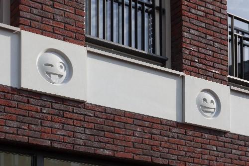 This building uses emoji cast in concrete as modern gargoyles