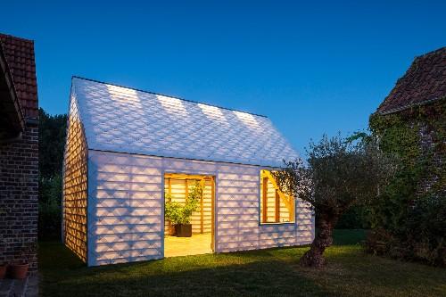 Simple backyard shed is a glowing retreat