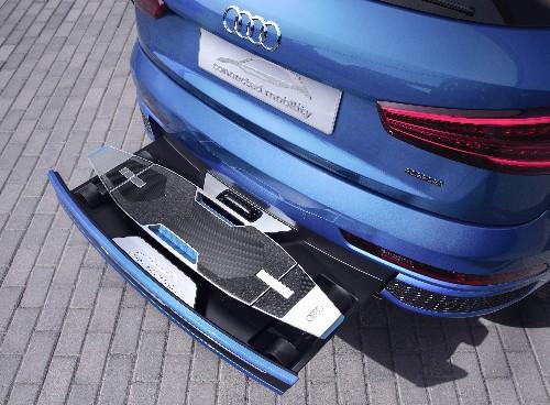 This Audi has a beautiful electric longboard hidden in its bumper