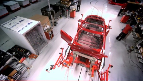 Watch robot arms massage a roll of metal into a Tesla Model S
