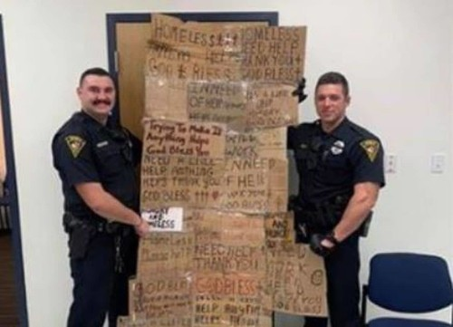 Two officers posed with 'homeless quilt' made from confiscated signs. Their chief apologized.
