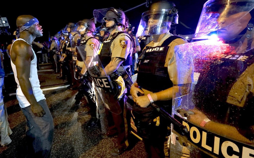 A protester yells at a police line shortly before shots were fired in a police-officer involved shooting in Ferguson