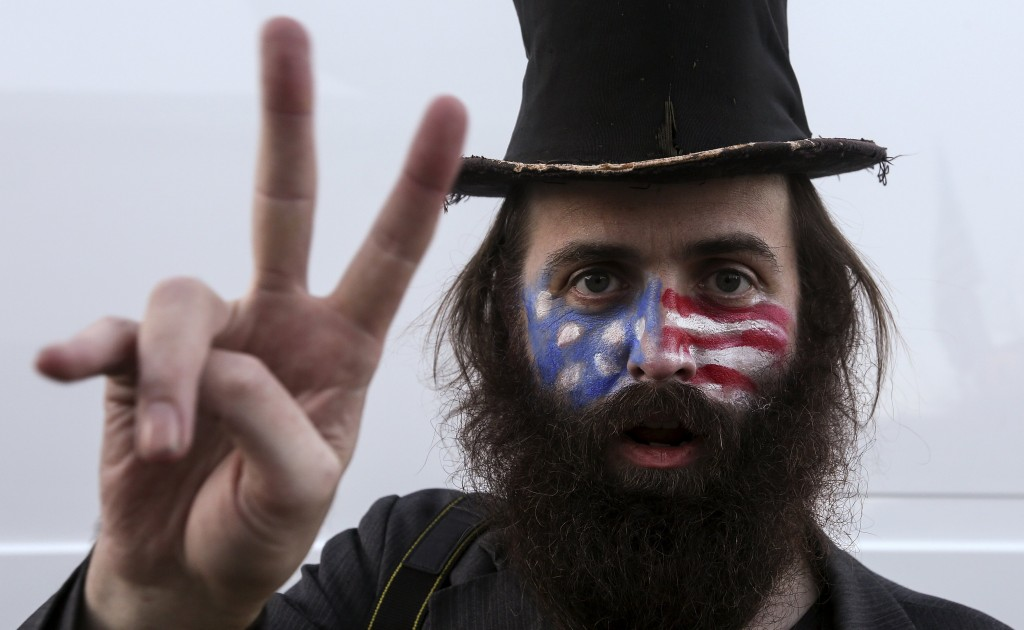 Rod Webber from Boston, with his face painted like the U.S. flag, makes a peace sign as he poses for a portrait outside Exeter Town Hall before a Marco Rubio presidential campaign rally in Exeter, New Hampshire, February 2, 2016. REUTERS/Carlo Allegri