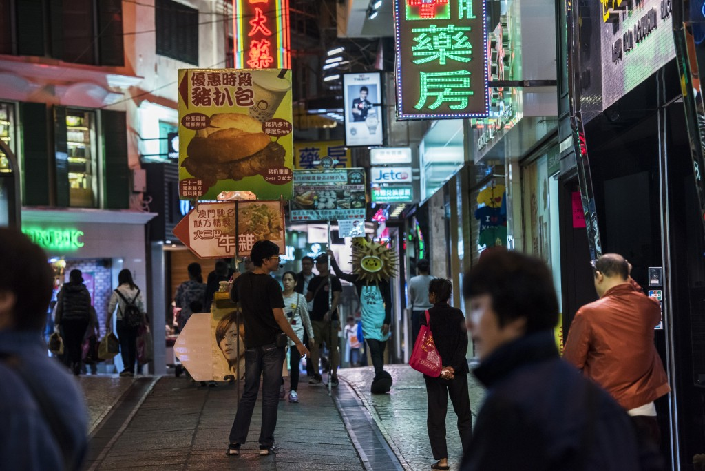 A man holds a sign advertising a restaurant on a street in Macau, China, on Tuesday, Dec. 1, 2015. Macau's casino revenue fell for the 18th straight month in November, as China's moves to curb illicit money flows from the mainland deterred the high-stakes players who rely on junket promoters for betting loans. Photographer: David Paul Morris/Bloomberg via Getty Images
