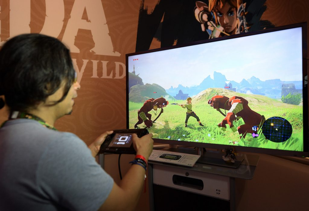 "LOS ANGELES, CA - JUNE 14: Gamers try out the new to play the new video game ""The Legend of Zelda: Breath of the Wild"" in the Nintendo booth during the annual E3 2016 gaming conference at the Los Angeles Convention Center on June 14, 2016 in Los Angeles, California. The Electronic Entertainment Expo will run from June 14 -16. (Photo by Kevork Djansezian/Getty Images)"