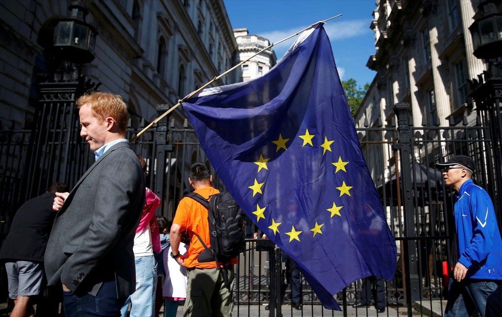 A man carries an EU flag outside Downing Street after Britain voted to leave the European Union. REUTERS/Neil Hall