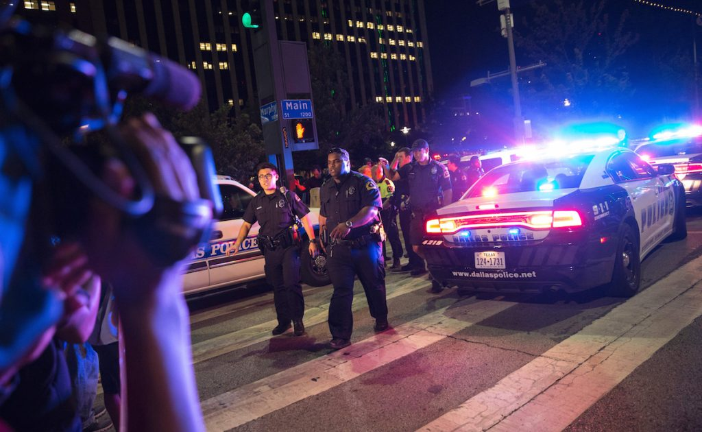 Bystanders stand near pollice baracades following the sniper shooting in Dallas on July 7, 2016. LAURA BUCKMAN/AFP/Getty Images