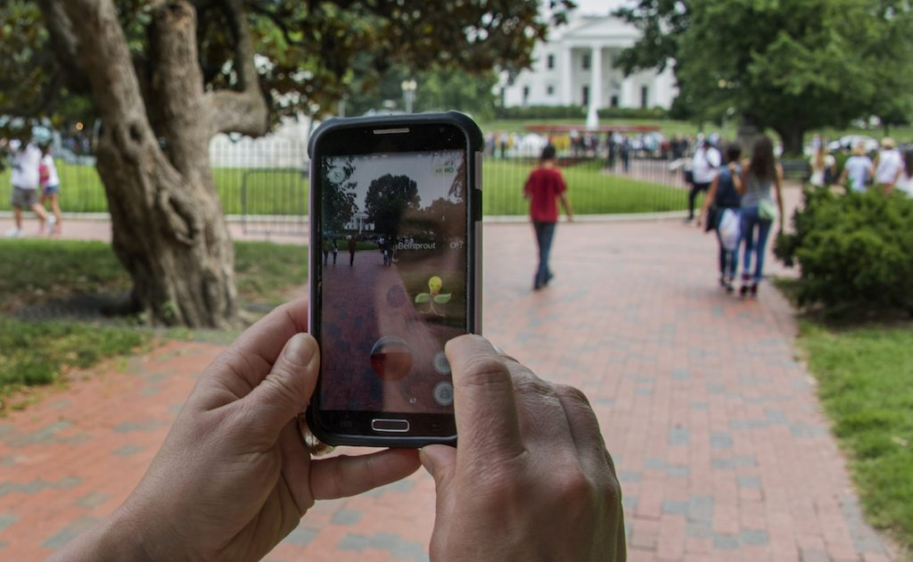 A woman holds up her cell phone as she plays the Pokemon Go game in Lafayette Park in front of the White House in Washington, DC, July 12, 2016. JIM WATSON/AFP/Getty Images