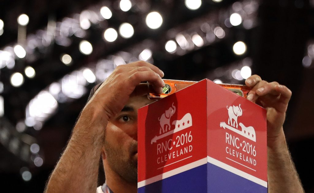 Daniel Shepherd levels a pole marking the section for delegates from the District of Columbia as preparations take place for the Republican National Convention inside Quicken Loans Arena in Cleveland, Ohio, Saturday, July 16, 2016. AP Photo/Patrick Semansky