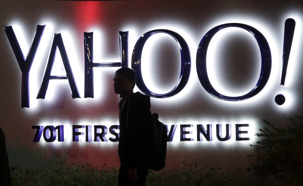A person walks in front of a Yahoo sign at the company's headquarters in Sunnyvale, Calif. AP Photo/Marcio Jose Sanchez, File