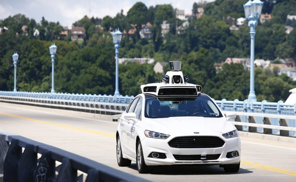 Uber employees test a self-driving Ford Fusion hybrid car, Thursday, Aug. 18, 2016, in Pittsburgh. Uber said that passengers in Pittsburgh will be able to summon rides in self-driving cars with the touch of a smartphone button in the next several weeks. The high-tech ride-hailing company said that an unspecified number of autonomous Ford Fusions with human backup drivers will pick up passengers just like normal Uber vehicles. Riders will be able to opt in if they want a self-driving car, and rides will be free to those willing to do it, spokesman Matt Kallman said. (AP Photo/Jared Wickerham)