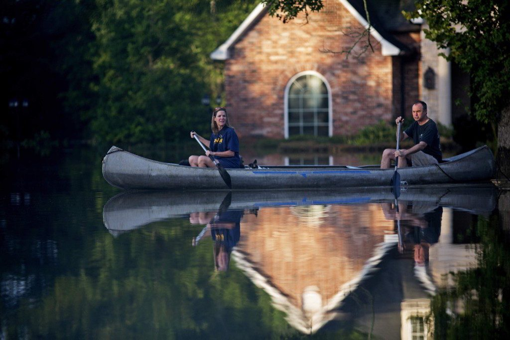 Danny and Alys Messenger canoe away from their flooded home after reviewing the damage in Prairieville, La. AP Photo/Max Becherer