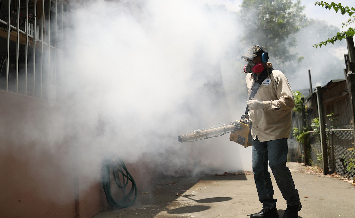 Carlos Varas, a Miami-Dade County mosquito control inspector, uses a Golden Eagle blower to spray pesticide to kill mosquitos on August 2, 2016 in Miami, Florida. Photo by Joe Raedle/Getty Images