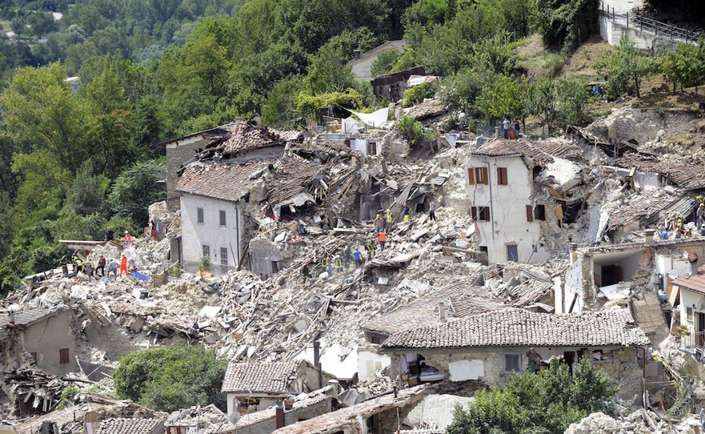 Rescuers search through debris of collapsed houses following an earthquake in Pescara del Tronto, Italy, Wednesday, Aug. 24, 2016. AP Photo/Sandro Perozzi