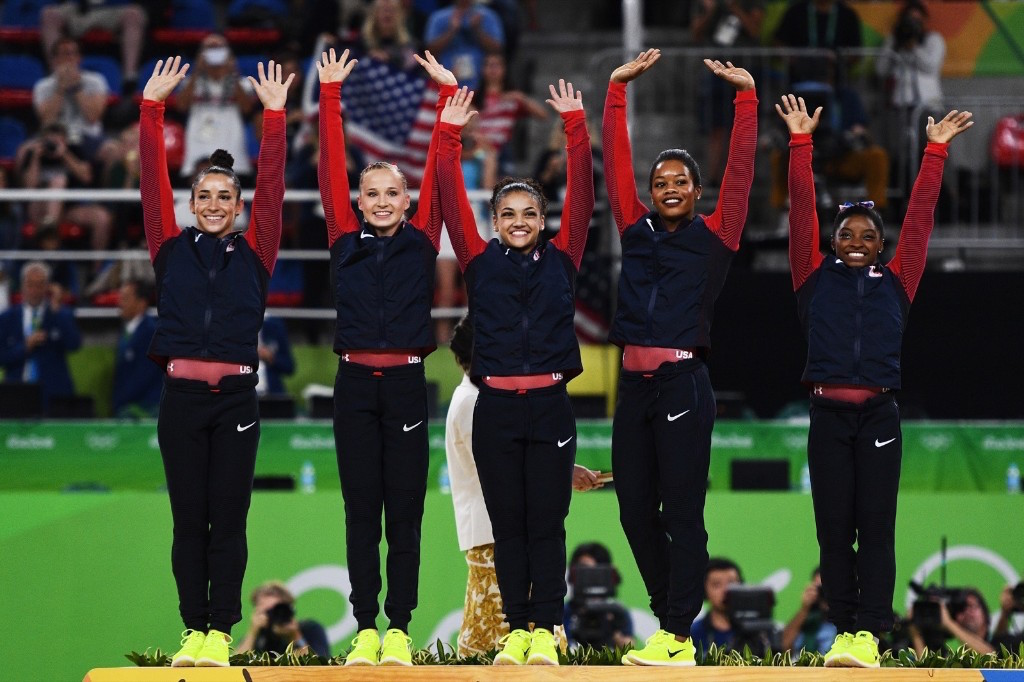 Gold Medalists Simone Biles, Gabby Douglas, Laurie Hernandez, Madison Kocian and Aly Raisman celebrate on the podium at the medal ceremony. David Ramos/Getty Images