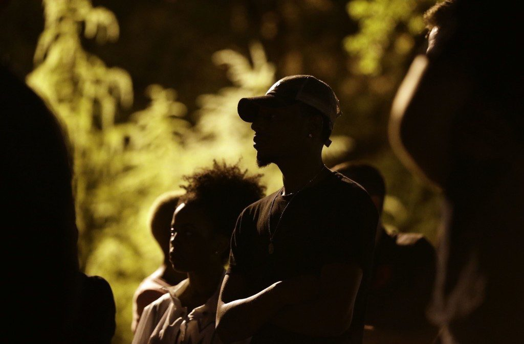 People gather for a vigil at the scene of Tuesday's police shooting of Keith Lamont Scott at The Village at College Downs apartment complex in Charlotte. AP Photo/Gerry Broome