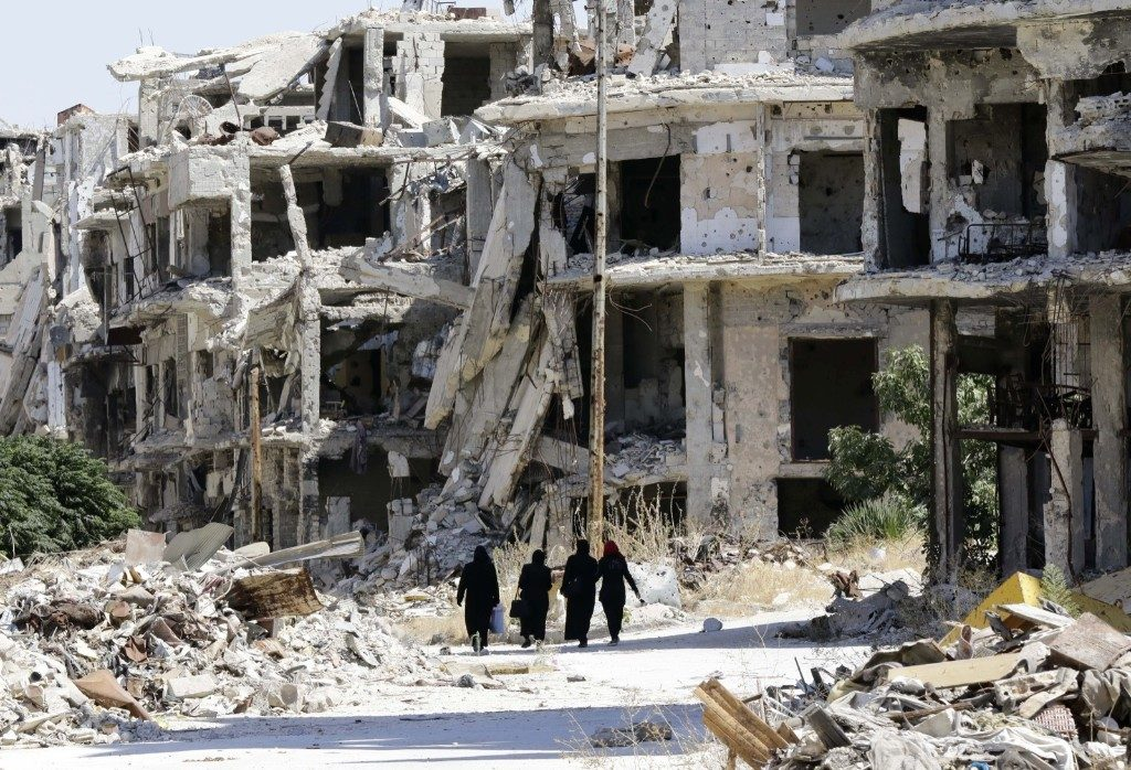 Syrian women walk between destroyed buildings in the government-held Jouret al-Shiah neighbourhood of Homs. LOUAI BESHARA/AFP/Getty Images