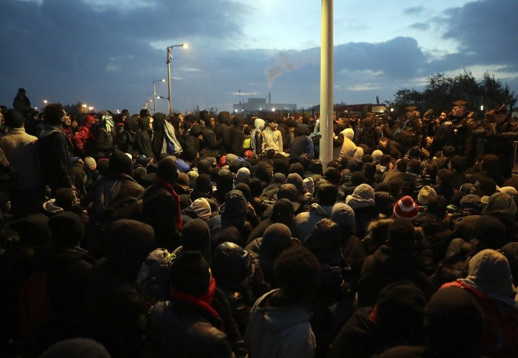 Migrants line-up to register at a processing centre. France began the mass evacuation of the makeshift migrant camp on Monday, a mammoth project to erase the humanitarian blight on its northern border, where thousands fleeing war or poverty have lived in squalor, most hoping to sneak into Britain. AP Photo/Matt Dunham
