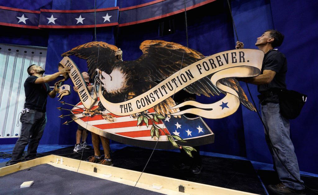 Workers install the eagle above the set for the last 2016 U.S. presidential debate in Las Vegas October 17, 2016. REUTERS/Rick Wilking
