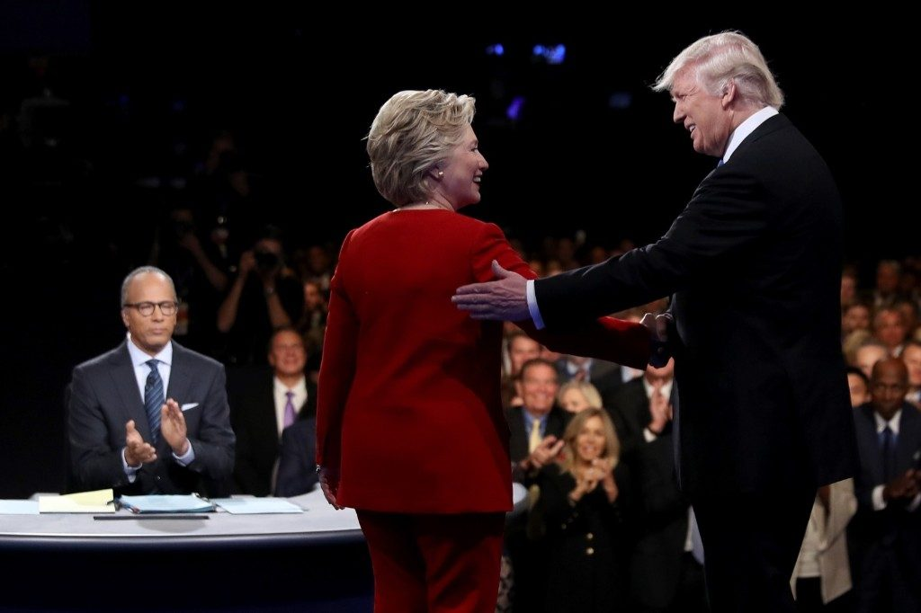 Hillary Clinton shakes hands with Donald Trump as moderator Lester Holt looks on. Joe Raedle/Getty Images
